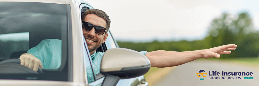Man in car with arm out the window smiling enjoying the ride.