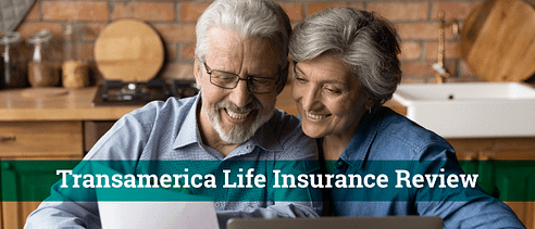 Smiling middle-aged couple sitting side-by-side looking at paperwork. They are inside a cabin-like home.