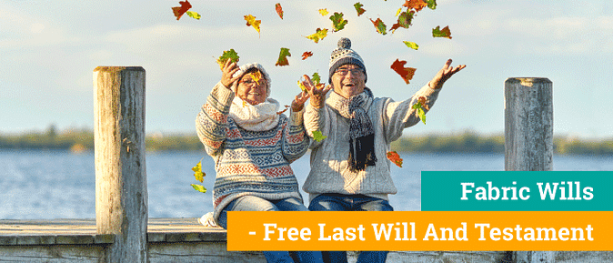 Couple with knit sweaters and hats sit on a dock throwing leaves