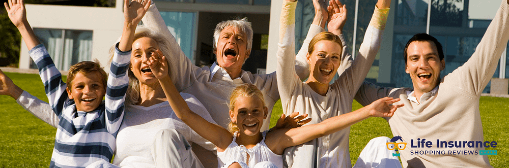 Grandparents, parents and kids with hands in air cheering while facing the camera